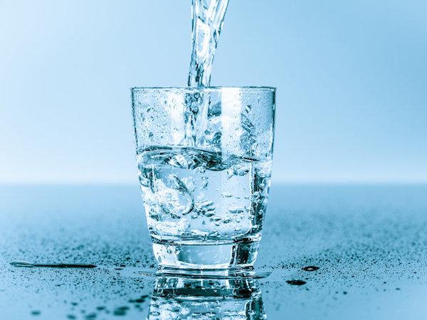 Egy pohárba töltenek vizet.