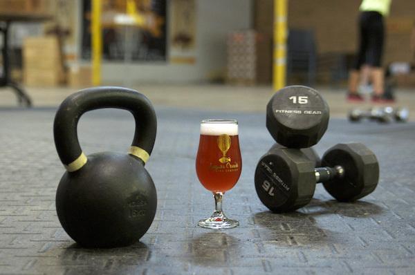 Kettlebell és kézi súlyzók mellett a földön egy nagy pohár sör.