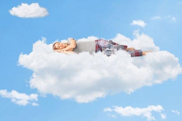 Felhőben alszik egy pizsamát viselő fiatal nő.