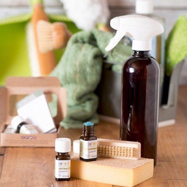 Sprcinis üveg, mellette kefék, szivacsok és illóolajok – a természetes takarítás kellékei.