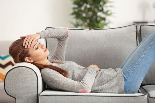Fiatal nő fáradtan a kanapéra dőlve fogja a fejét.