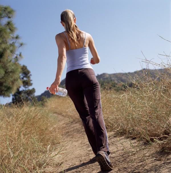 Fiatal lány gyalogol egy üveg ásványvízzel egy ösvényen a természetben.