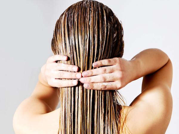 Hajpakolást símít hajára egy hölgy.