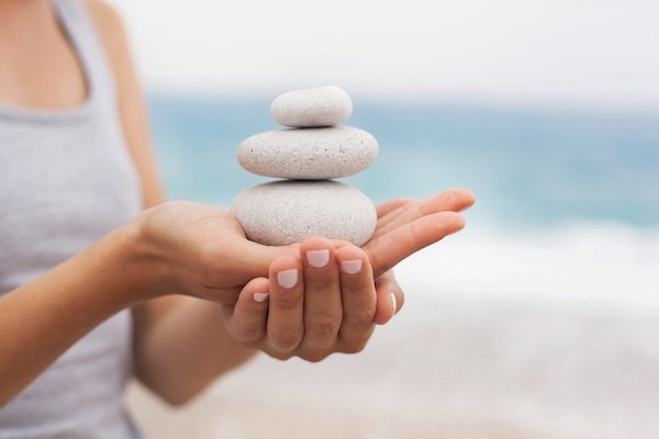 Nyitott tenyerében három egymásra rakott követ tart egy nő, a háttérben a tenger.