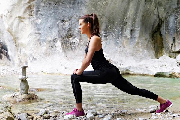 Jógagyakorlatokat végez egy fiatal nő vízpart mellett.