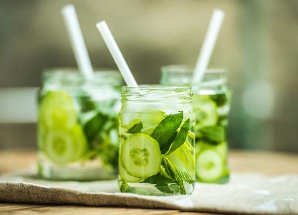 Uborkával és fűszernövényekkel dúsított ízesített víz kis üvegekbe töltve, bennük szívószál.