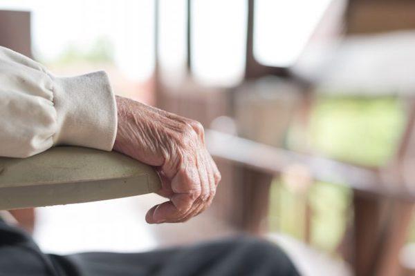 Idős ember fogja egy szék karfáját.