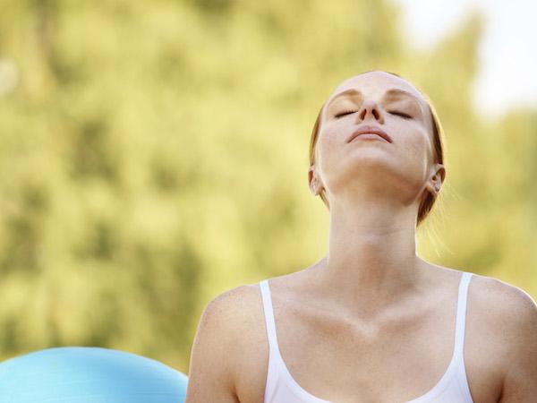 Légzőgyakorlatot végez egy fiatal nő, fejét az ég felé emeli belégzéskor.