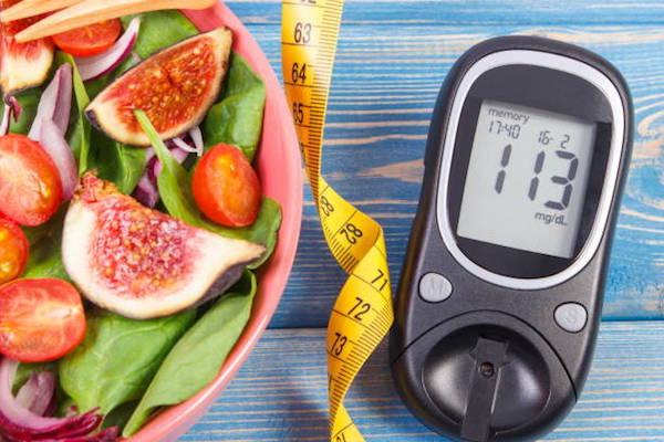 Fügés saláta spenóttal, koktélparadicsommal, lila hagymával, mellette centiméter és vércukorszintmérő.
