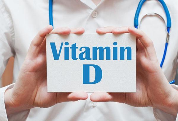 Orvos kék sztetoszkóppal a nyakában egy D-vitamin feliratú táblát mutat.