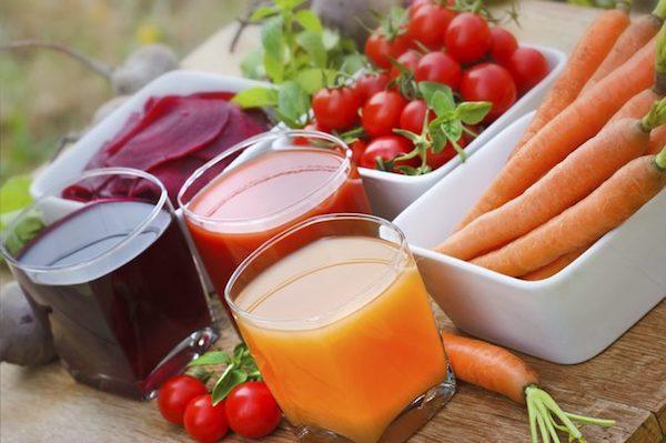 Cékla, paradicsom, sárgarépa és a belőlük készült frissen facsart levek üvegpoharakban.