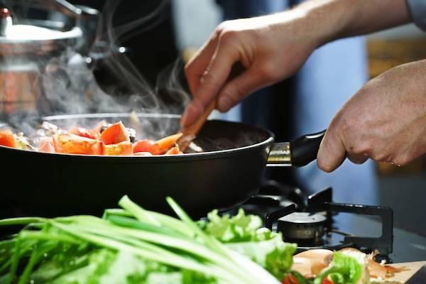 Serpenyőben sütnek különféle zöldségeket otthon.