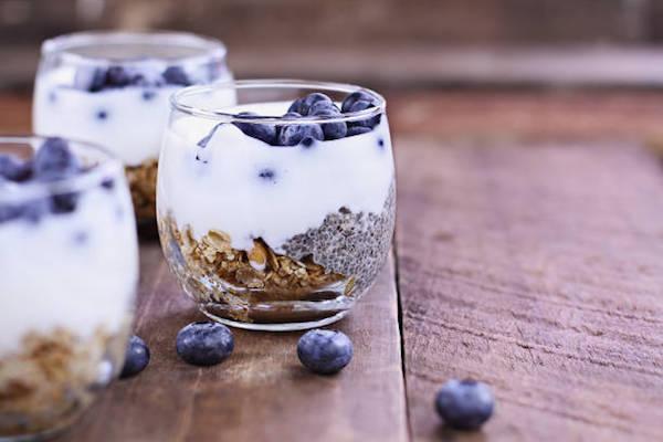 Egészséges reggeli: müzli, rajta joghurt vagy kefir, a tetején áfonya és chiamag.