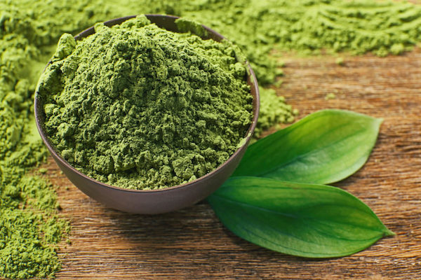 Porított chlorella alga kis tálban, mellette két zöld levél.