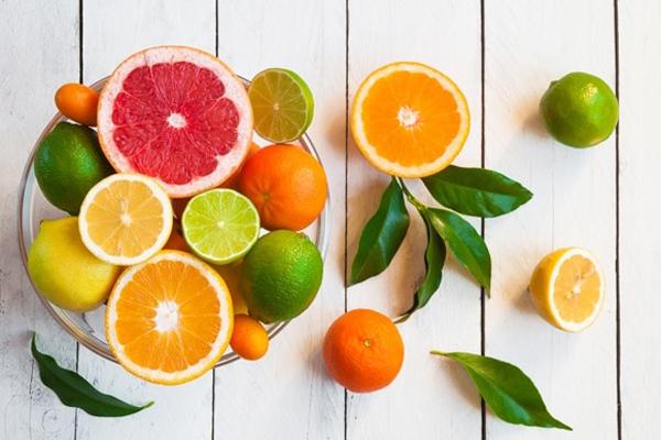 Különféle citrusfélék egy fehér asztalon: grépfrút, lime, citrom, mandarin és narancs.