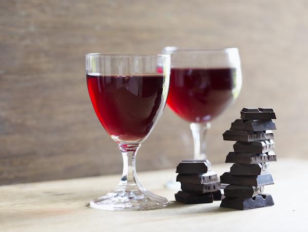 Két pohár vörösbor, mellette több kocka étcsoki egymásra rakva.