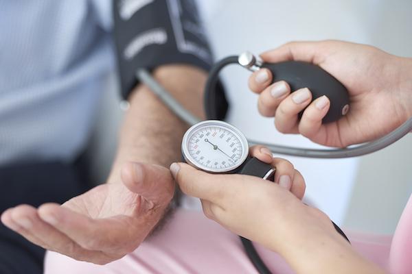 Mandzsettás vérnyomásmérés egy idősebb férfi karján.