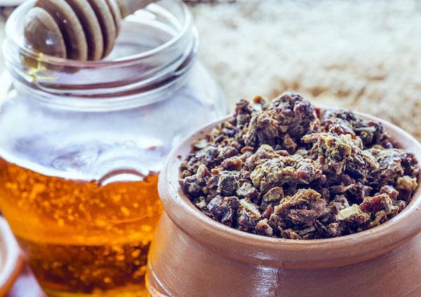 Agyag edénykében propolisz, mellette egy üveg méz, benne mézkanál.