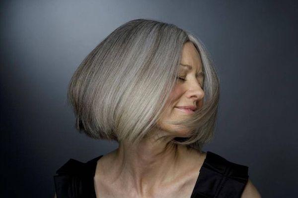 Ősz hajú idősebb, mosolygósabb hölgy.