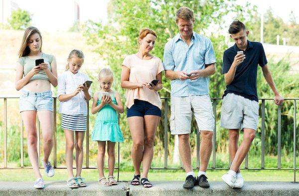 Az egész család, kicsitől a nagyig nyomkodja egymás mellett a telefonját.