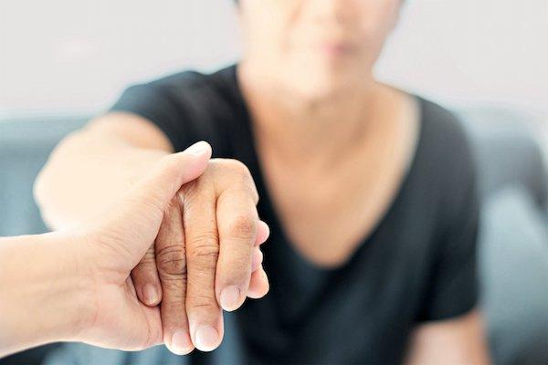Alzheimeres hölgynek segítenek a felállásban.