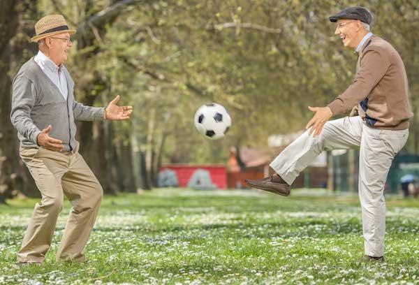 Két idős, jókedvű öregúr rúgja a focilabdát a füvön.