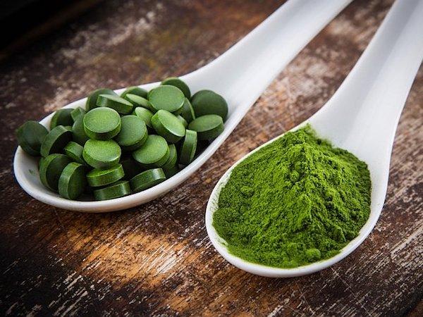 Chlorella alga tabletta és por alakban egy-egy fehér kanálban.