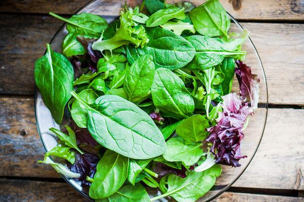 Zöld leveles zöldségek egy üvegtányéron.