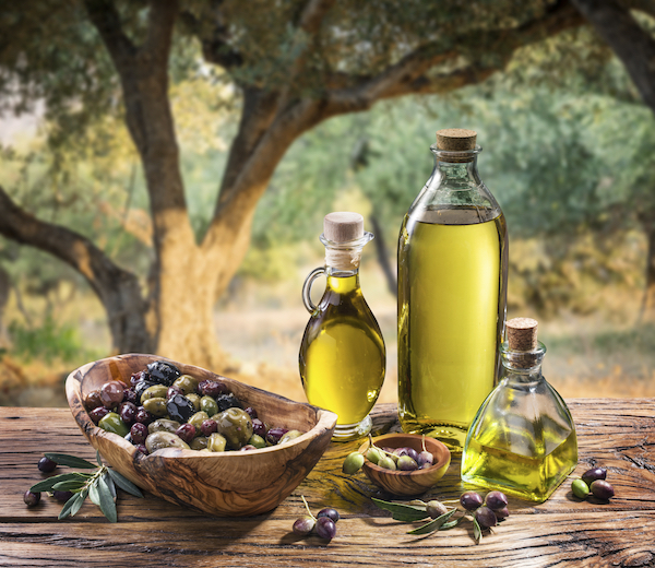 Olívaolaj gyönyörű üvegekben, mellettük bambusztálakban friss olívabogyók, a háttérben olajfák.