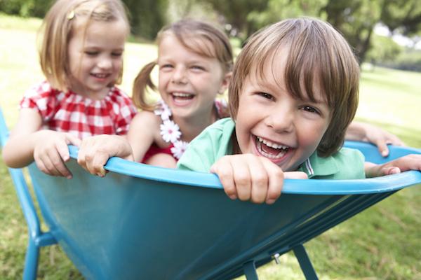 Három kisgyerek ül egy kék talicskában és tiszta szívből nevetnek.
