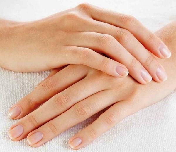 Ápolt kezeit teszi egymásra egy fiatal nő.