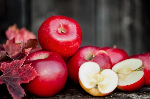 Őszi levelek mellett piros almák.