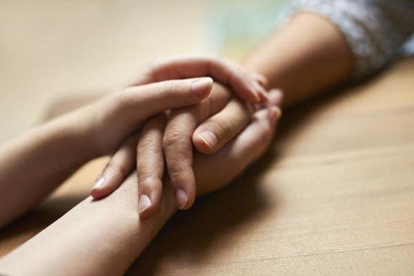 Egy férfi és egy női kéz összefonódása az asztalon.
