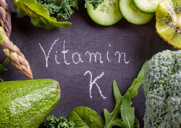 Fekete táblára K-vitamin felirat, körülötte a vitamint tartalmazó zöldségek és gyümölcsök: uborka, kivi, avokádó, brokkoli, zöld leveles saláták, spárga.