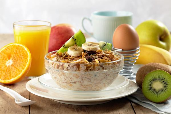 Egészségges reggeli: müzli, főtt tojás, narancslé, gyümölcsök.