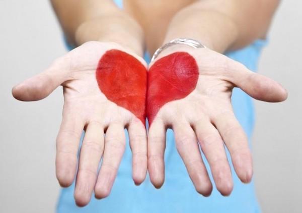 Egy hölgy felfelé fordított tenyereire egy szív van felfestve.