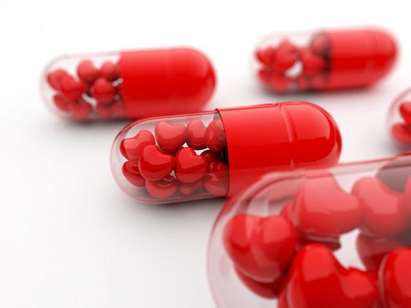 Piros színű, szív alakú étrend-kiegészítők kapszulába zárva.
