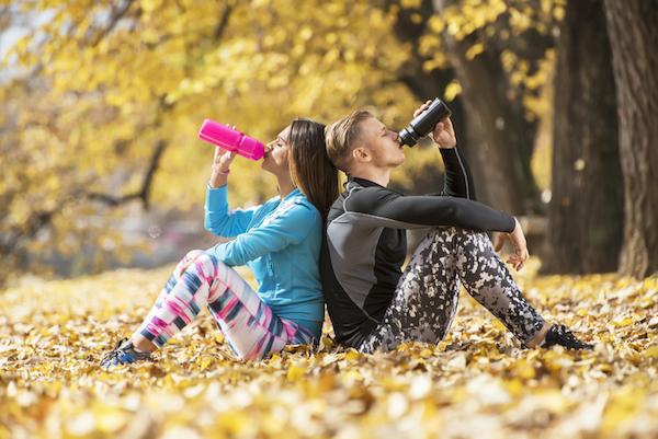 Őszi avarban egymásnak háttal ülve iszik kulacsából edzése után egy fiatal pár.