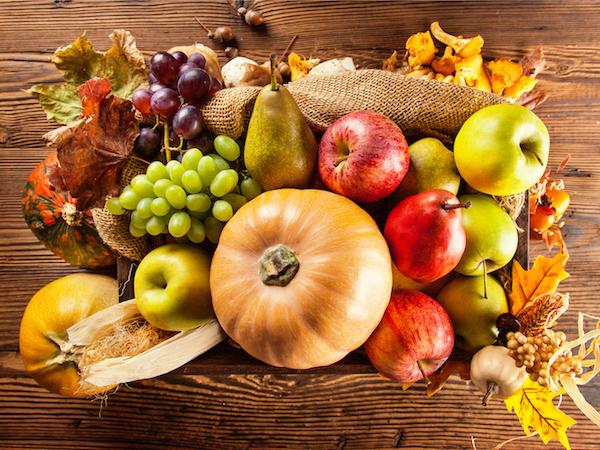 Őszi zöldségek és gyümölcsök zsákvászonon egy asztalon: sütőtök, alma, körte, szőlő, kukorica.