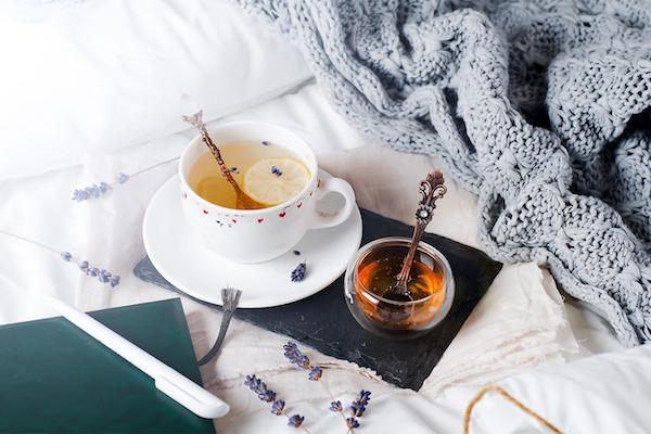 Eg csésze tea az ágyban, mellette méz, szürke meleg takaró, jegyzetfüzet, toll.