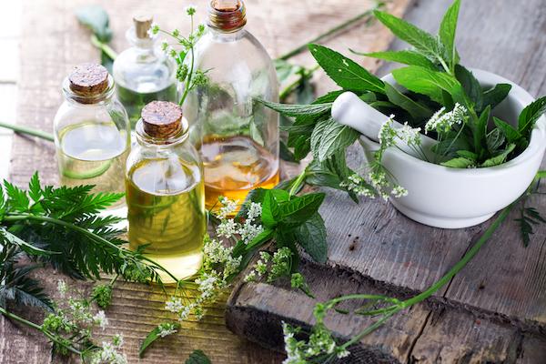 Gyógynövények mozsárban, mellettük a belőlük kinyert illóolajak üvegekben.