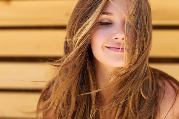 Kedves arcú, szép, barna hajú lány képe.