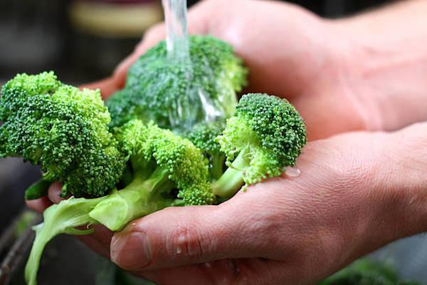 Rózsáira szedett brokkolit mos tenyerében folyó víz alatt egy férfi.