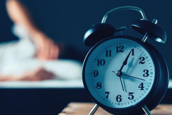 Fekete ébresztőóra hajnalban, háttérben egy párnáján ébren hánykolódó férfi.