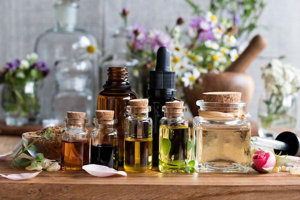 Különféle színű illóolajak mindenféle típusú üvegekben, a háttérben a virágok, melyekből az olajok készültek.