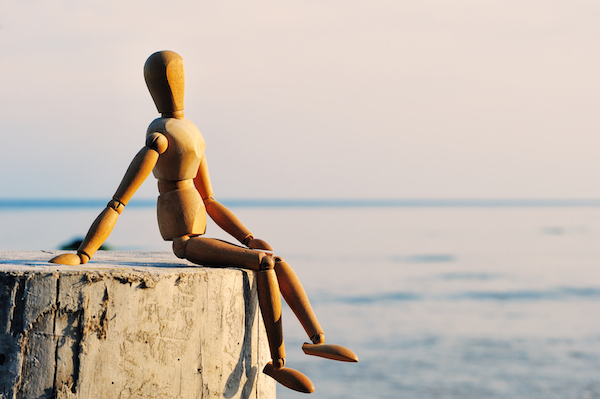 Fa figura ül egy fadarabon a tengert szemlélve.