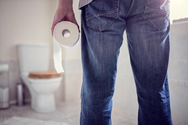 Farmeres férfi WC-papírral a kezében igyekszik a toalettre.