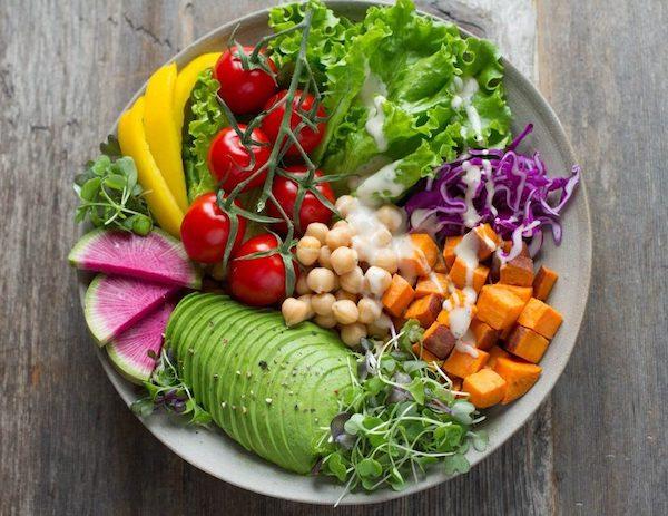 Friss zöldségek és gyümölcsök, csírák egy tányéron szépen összerendezve.