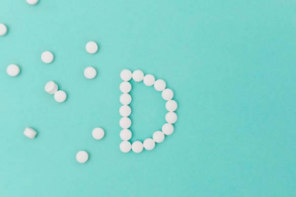 Türkiz alapon fehér D-vitamin tabletták D betűt formázva.