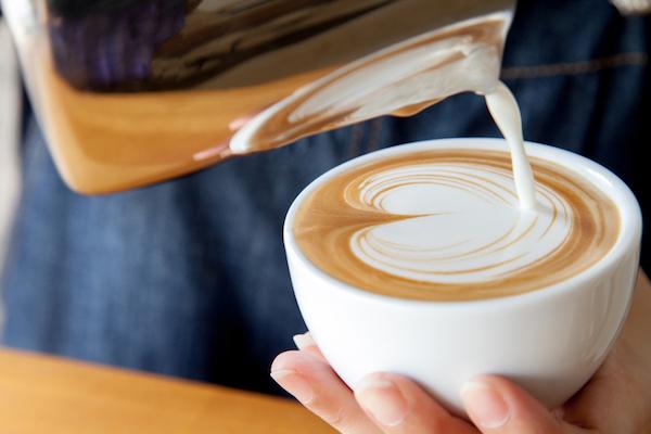 Egy csésze kávéra óvatosan öntik a tejszínt, ami egy szívet mintáz meg.